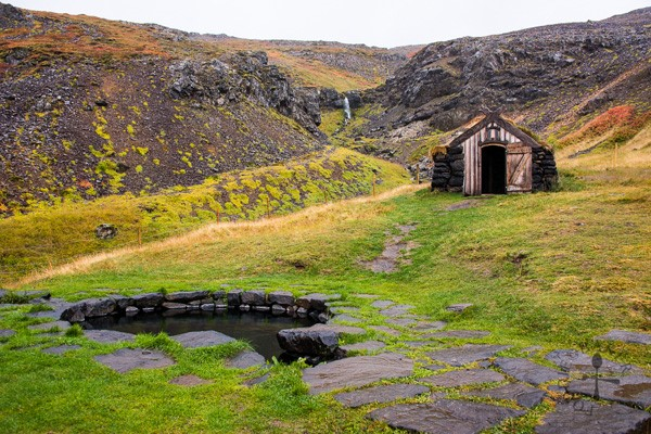 Guðrúnarlaug natural baths with a tiny wooden house behind in Iceland