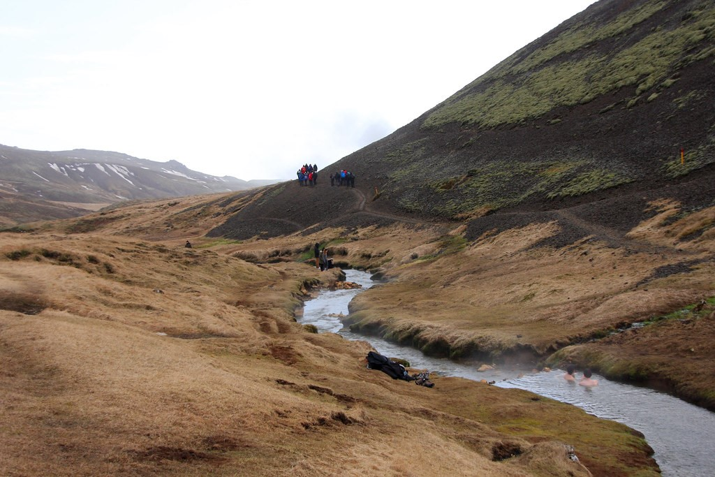 people bathing in the Reykjadalur hot river on the foreground and people hiking in the background