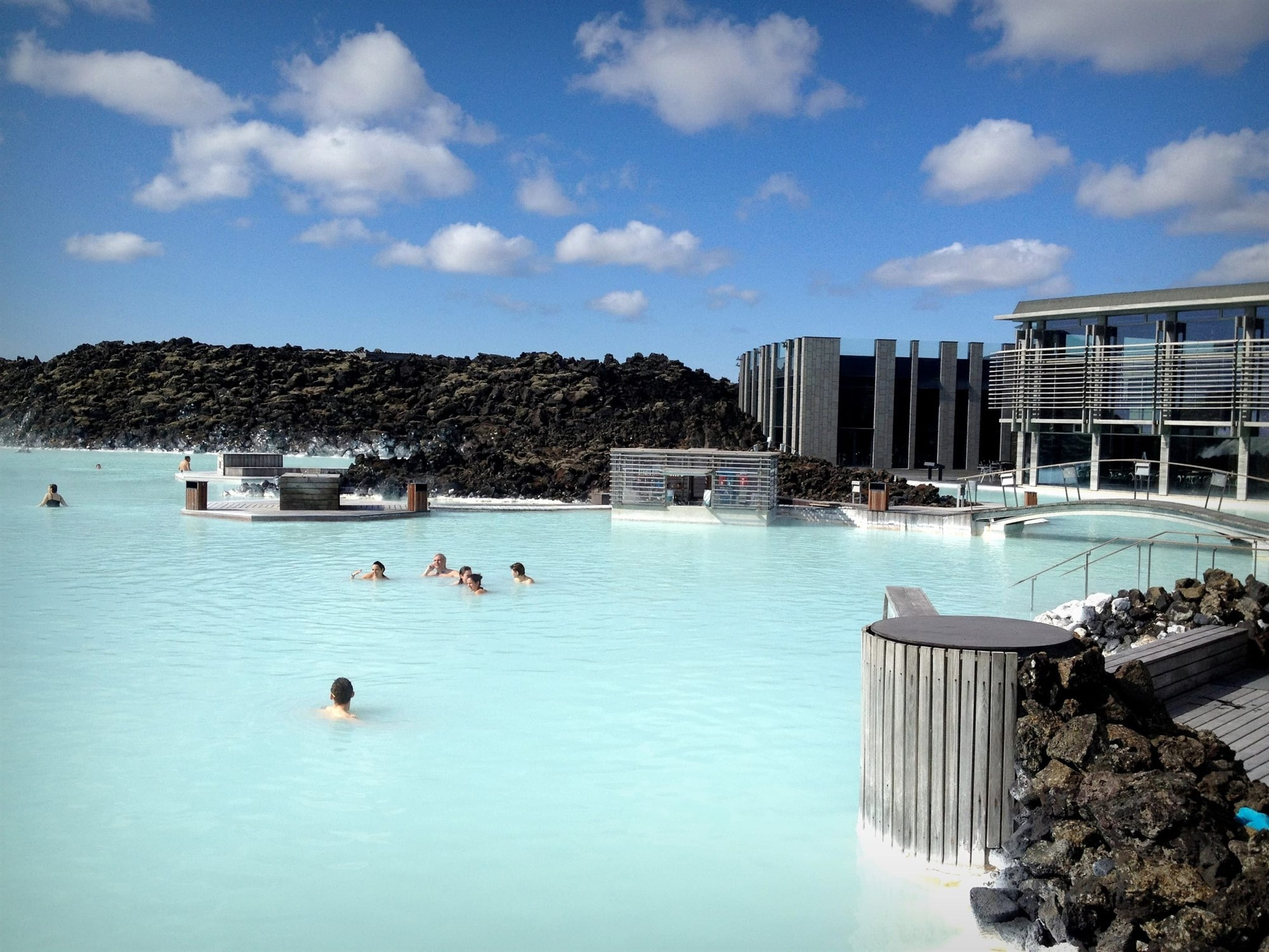 people enjoying the milky blue waters of blue lagoon in a sunny afternon